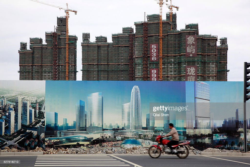 A man rides a motorbike past new apartment building developments seen standing behind propaganda for the Chinese Communist Party in Kunshan Jiangsu...