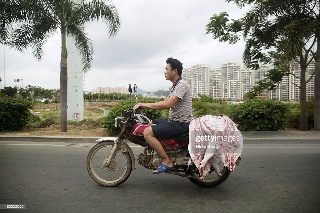 A man rides a motorcycle carrying a halved pig's carcass in the Sanya City district of Sanya, Hainan Province, China, on Sunday, April 6, 2014. The yuan is poised to recover from declines that have made it Asia's worst-performing currency as China seeks to prevent an exodus of capital that would threaten economic growth, according to the most accurate forecasters. Photographer: Brent Lewin/Bloomberg via Getty Images