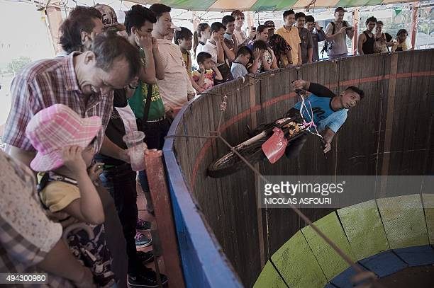 A man rides a motorcycle in a cylinder to entertain visitors during the annual buffalo races in Chonburi southeast of Bangkok on October 26 2015...