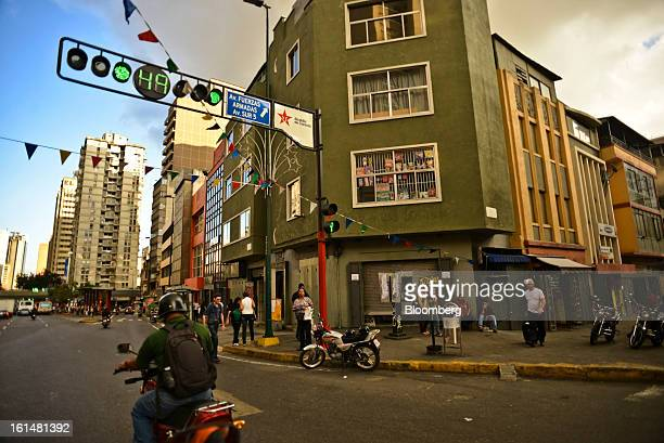 A man rides a motorcycle in downtown Caracas Venezuela on Monday Jan 14 2013 Venezuela's central bank is considering ways to expand the supply of...