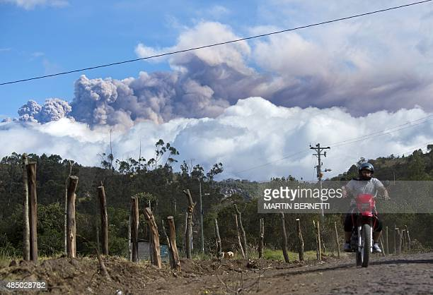 A man rides a motorcycle in Sangolqui Ecuador with ashes spewed by the Cotopaxi volcano in the background on August 23 2015 A dozen towns of central...