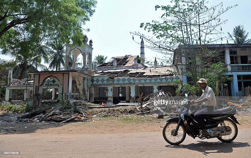 A man rides a motorcycle past a destroyed mosque after sectarian violence spread through central Myanmar, in Okpho, Bago division on March 28, 2013. Myanmar's Muslim leaders have appealed to President Thein Sein to take swift action to quell religious violence, accusing security forces of standing by as rioters went on a rampage. AFP PHOTO/Ye Aung THU