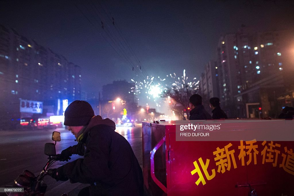 A man rides a motorcycle past people lighting fireworks on a street in Beijing on February 7, 2016, the eve of the Lunar New Year. China marks the beginning of the Lunar New Year, the Year of the Monkey, on February 8. / AFP / FRED DUFOUR