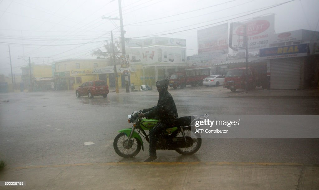 TOPSHOT - A man rides a motorcyle along a flooded street in Punta Cana, in the Dominican Republic, as Hurricane Maria approaches on September 20, 2017. The government of the Dominican Republic told people to stay home from their public and private sector jobs on Thursday, when the hurricane is expected to hit the island. / AFP PHOTO / Erika SANTELICES