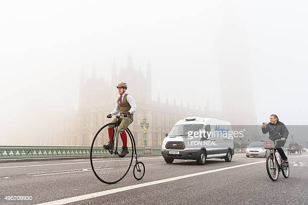 A man rides a Penny Farthing bicycle past the Houses of Parliament in Westminster shortly after beginning the 119th 'Veteran Car Run' from Hyde Park...