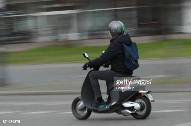 A man rides a rented Coup electric sharing scooter in the city center on November 14 2017 in Berlin Germany A number of companies have plunged into...