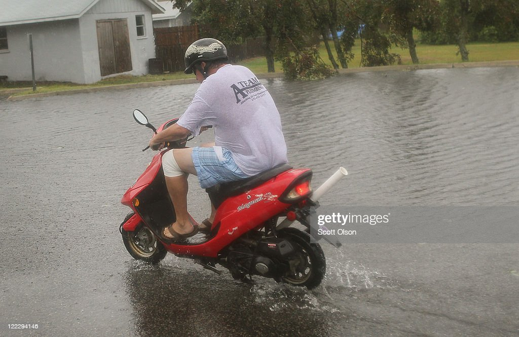 A man rides a scooter during Hurricane Irene August 27, 2011 in Kill Devil Hills, North Carolina. Hurricane Irene hit Dare County, which sits along the Outer Banks and includes the vacation towns of Nags Head, Kitty Hawk and Kill Devil Hills, as a Category 1 hurricane around mid-day today.