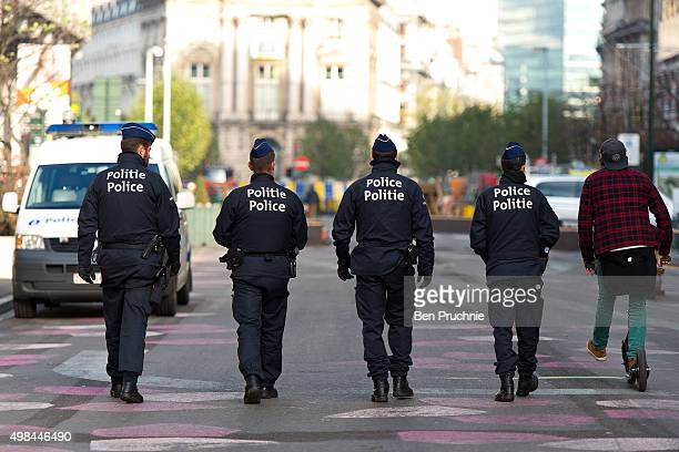 A man rides a scooter past four armed policemen patrolling the Boulevard Anspach on November 23 2015 in Brussels Belgium Security has been tightened...