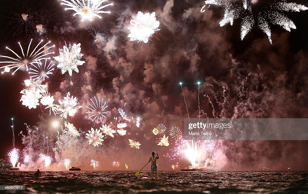 A man rides a stand up paddle board as fireworks explode above him during New Year's festivities on Copacabana Beach on January 1, 2015 in Rio de Janeiro, Brazil. Up to 2 million revelers were expected on Copacabana Beach to watch the annual New Year's fireworks display which this year coincided with the start of the city's 450th anniversary celebrations.