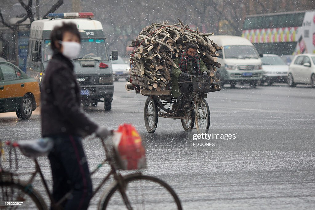 A man rides a tricycle laden with logs along a road during snowfall in Beijing on December 12, 2012. Snowfall hit the Chinese capital with seasonal minus temperatures forecast to bring more later in the week. AFP PHOTO / Ed Jones
