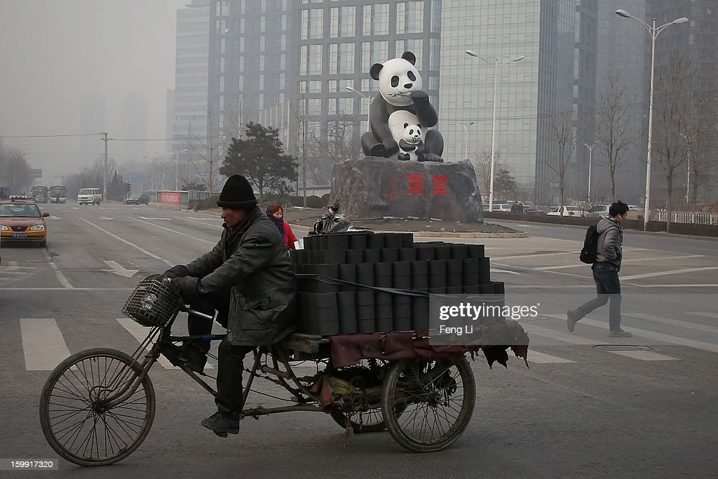 A man rides a tricycle to transport coal through a panda sculpture during severe pollution on January 23, 2013 in Beijing, China. The air quality in Beijing on Wednesday hit serious levels again, as smog blanketed the city.