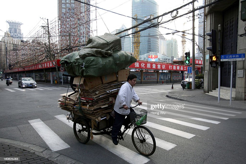 A man rides a tricycle transporting recycle cardboard on February 3, 2013 in Shanghai, China.