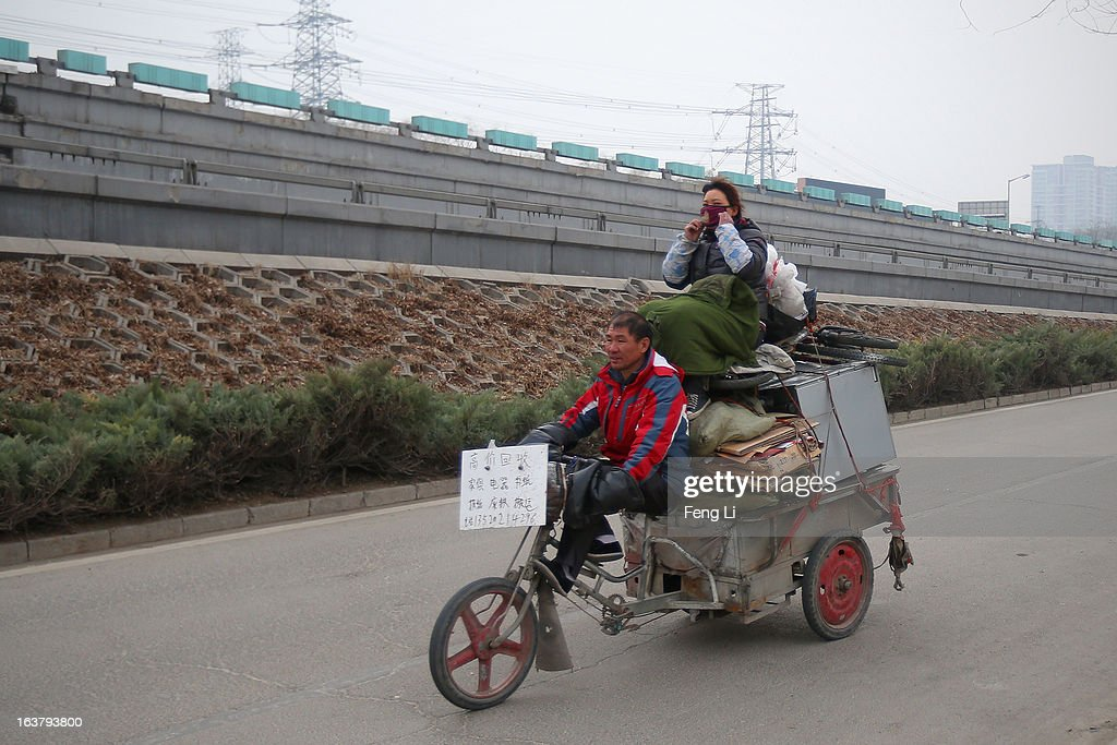 A man rides a tricycle with his wife wearing the mask on the street on March 16, 2013 in Beijing, China. Clearing urban air pollution has become a big concern during the National People's Congress.