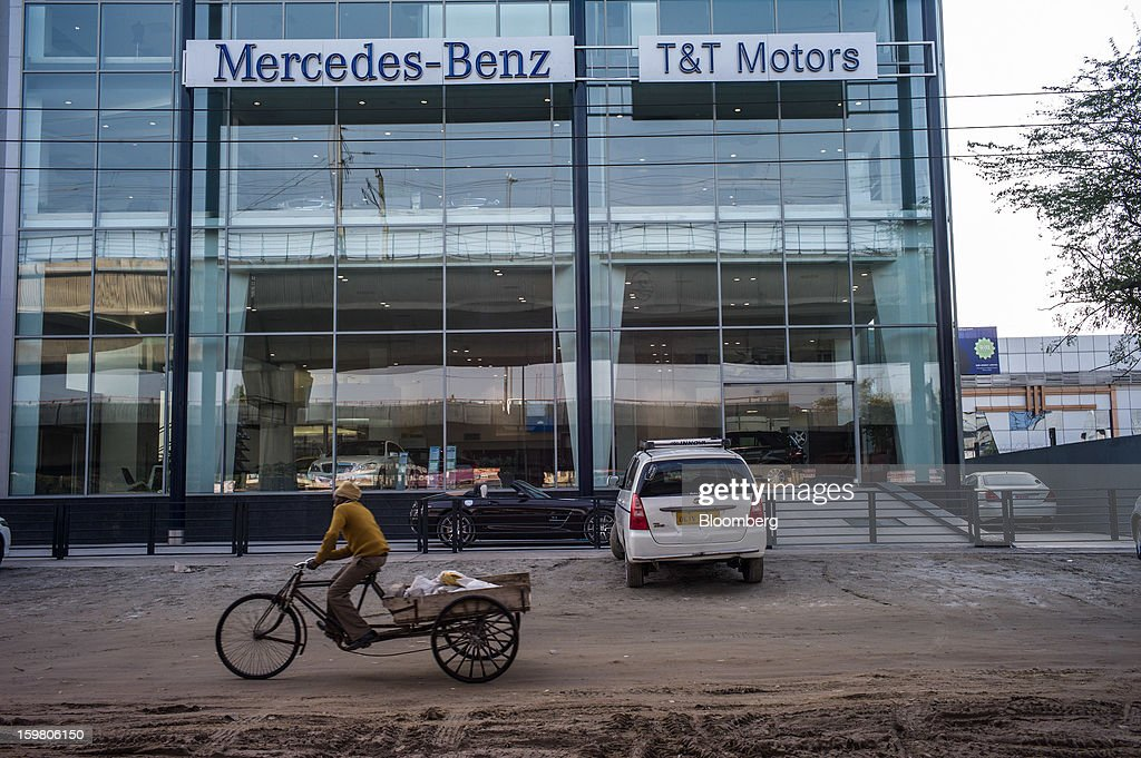 A man rides a trishaw past the newly opened T&T Motors Ltd. Mercedes-Benz India flagship dealership in New Delhi, India, on Saturday, Jan. 19, 2013. The Indian Finance Ministry projects Asia's third-largest economy will expand as little as 5.7 percent in the 12 months to March 31, which would be the weakest pace in a decade. Photographer: Sanjit Das/Bloomberg via Getty Images