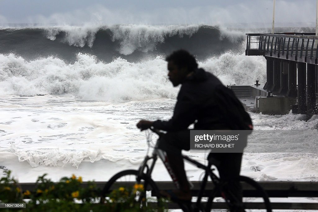 A man rides along the sea on the northwestern coast of French Indian Ocean island of La Reunion on January 31, 2013 near Saint-Paul, as high waves hit the coastline, caused by the cyclone Felleng at 530 Km north of the island. BOUHET