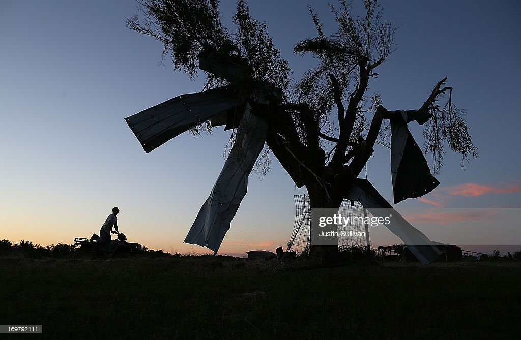 A man rides an ATV by a tree that has metal siding hanging from it after a series of tornadoes ripped through the area a day earlier on June 1, 2013 in El Reno, Oklahoma. A series of tornadoes ripped through the area on Friday evening killing at least nine people, injuring many others and destroying homes and buildings.