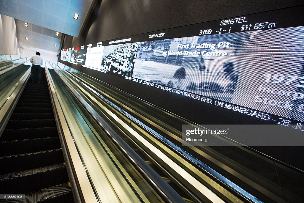 A man rides an escalator past an electronic screen at the Singapore Exchange Ltd. (SGX) headquarters in Singapore, on Tuesday, June 28, 2016. Days after the surprise U.K. vote for Brexit started roiling global markets, prospects for greater monetary and fiscal stimulus are becoming clear in Asia, even as the region's relative growth dynamism offers it resilience. Photographer: Nicky Loh/Bloomberg via Getty Images