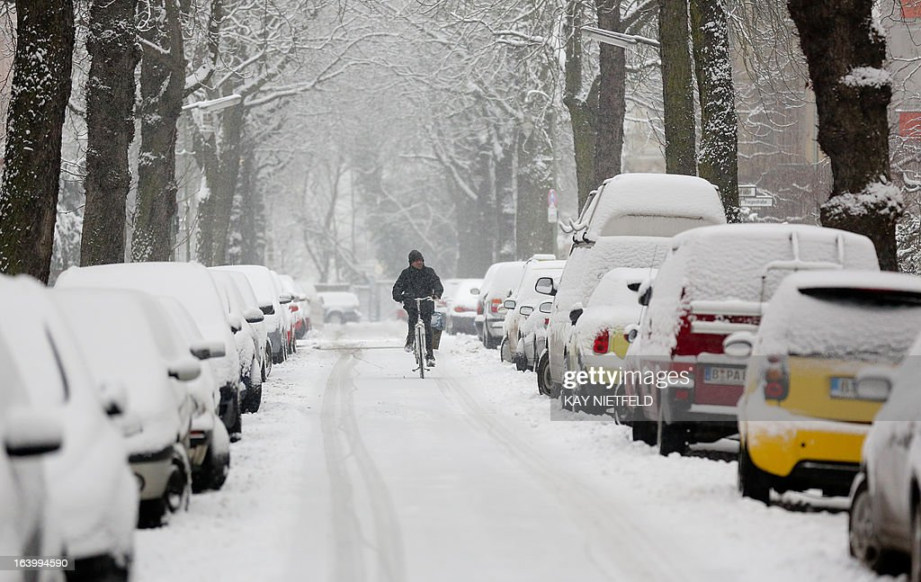 A man rides bicycle in a snow-covered street during a snowfall in Berlin, on March 19, 2013. OUT +++