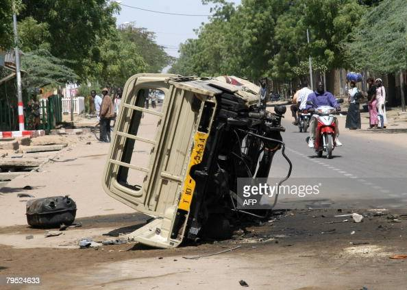 A man rides by a motorcycle by a damaged vehicle in the capital city N'Djamena on February 5 2008 after heavy fighting between government forces and...