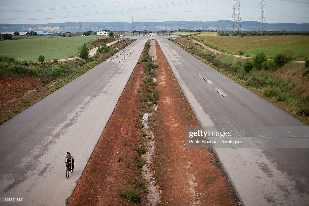 A man rides his bicycle a long the MP-203 highway project near Mejorada del Campo on May 15, 2013 in Madrid, Spain. The MP-203 highway, which was built to decongest the Barcelona highway (A-2), has remained unfinished for 6 years after an initial investment 70 millions Euro between 2005 and 2007. Despite the completion of around 70 percent of the 12.5 kilometer project it was stopped after issues arose with the Madrid - Barcelona high speed railway and the connection to the R-3 highway.