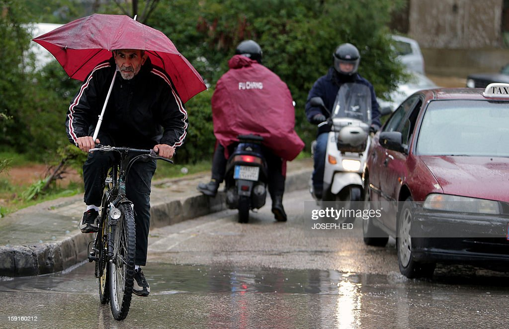 A man rides his bicycle along a street in Beirut on January 9, 2013 as heavy rains and high speed winds hit the country. A met office official at Beirut airport said the storm would continue and that lower temperatures would result in snowfall in the mountains as low as 300 metres.