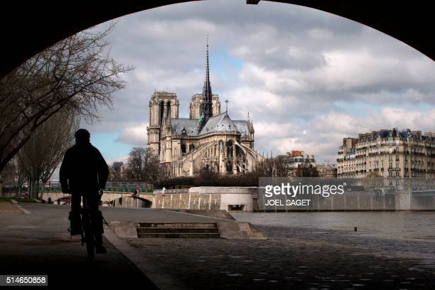A man rides his bicycle along the Seine banks close to Notre Dame Cathedral in Paris on March 10 2016 / AFP / JOEL SAGET