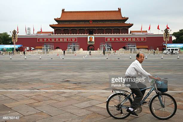 Man rides his bicycle before competitors run in front of the Forbidden City at Tiananmen Square in the Womens Marathon during day nine of the 15th...