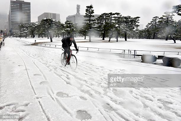 A man rides his bicycle on a snow covered road in Tokyo on January 18 2016 Heavy snow blanketed Tokyo metropolitan area and transportation systems...