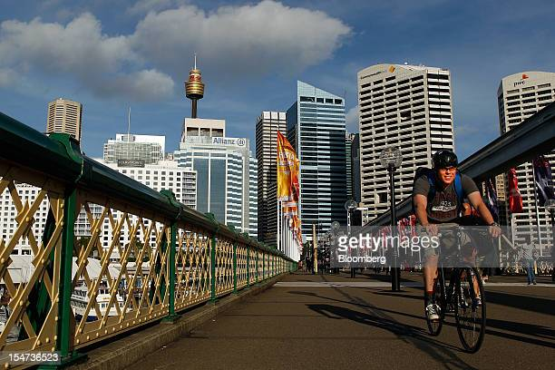 A man rides his bicycle on the Pyrmont Bridge as commercial buildings stand in the central business district in Sydney Australia on Tuesday Oct 23...