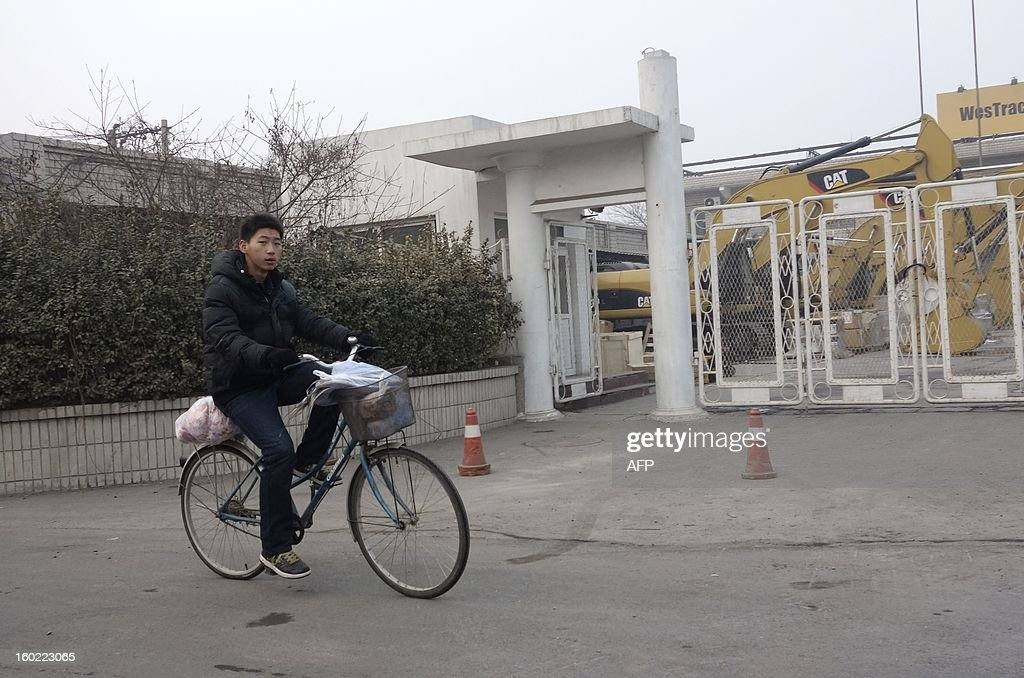 A man rides his bicycle past a Caterpillar yard in Beijing on January 28, 2013. Caterpillar's revelation it found fake accounts at a just-acquired Chinese firm which will cost it hundreds of millions of dollars is a cautionary tale for those looking to enter the hugely promising market. The US equipment giant said this month it would take a 580 million USD charge after uncovering 'accounting misconduct' at Siwei Mechanical and Electrical Manufacturing Co., which it bought last year for at least 650 million USD. AFP PHOTO / WANG ZHAO