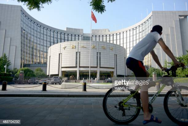 A man rides his bicycle past the People's Bank of China in Beijing on August 12 2015 China cut the yuan's value against the US dollar for the second...