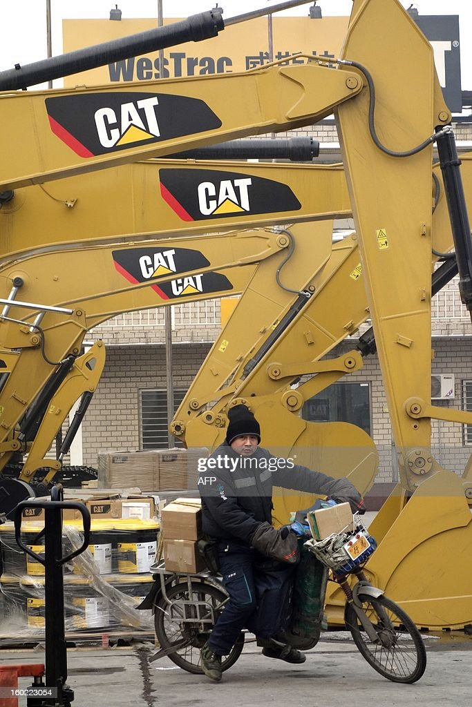 A man rides his bicycle through a Caterpillar yard in Beijing on January 28, 2013. Caterpillar's revelation it found fake accounts at a just-acquired Chinese firm which will cost it hundreds of millions of dollars is a cautionary tale for those looking to enter the hugely promising market. The US equipment giant said this month it would take a 580 million USD charge after uncovering 'accounting misconduct' at Siwei Mechanical and Electrical Manufacturing Co., which it bought last year for at least 650 million USD. AFP PHOTO / WANG ZHAO
