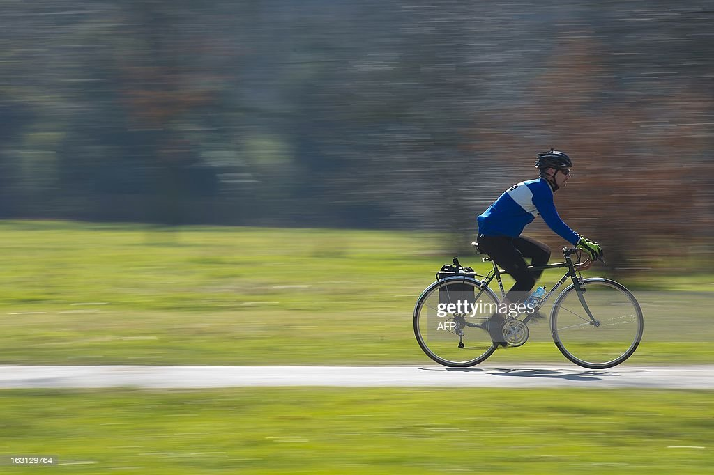 A man rides his bicycle through Kensington Gardens during sunny weather in London on March 5, 2013. Areas of Southern England experienced the mildest day of the year so far, with temperatures hovering around 15 degrees celcius. AFP PHOTO / BEN STANSALL