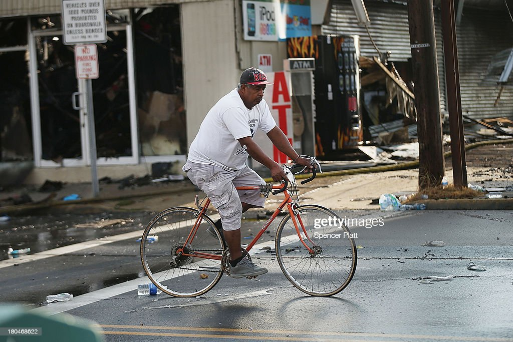 A man rides his bike at the scene of a massive fire that destroyed dozens of businesses along an iconic Jersey shore boardwalk on September 13, 2013 in Seaside Heights, New Jersey. The 6-alarm fire began in a frozen custard stand on the recently rebuilt boardwalk around 2:00 p.m. on Thursday, September 12, and quickly spread in high winds. While there were no injuries reported, many businesses that had only recently re-opened after Hurricane Sandy were destroyed in the blaze.