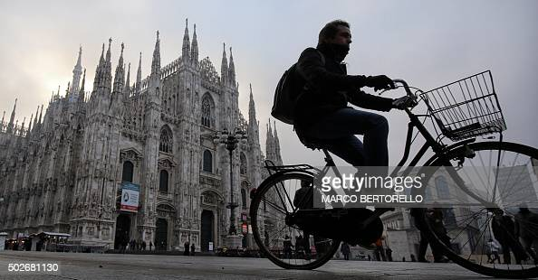 A man rides his bike near the Duomo in Milan on December 28 2015 Drivers in Milan will face a limit on daytime travel three days as the northern...