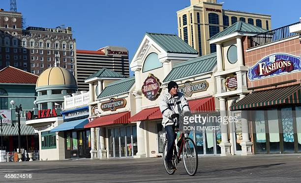 A man rides his bike on the boardwalk November 8 2014 in Atlantic City New Jersey AFP PHOTO/Don Emmert