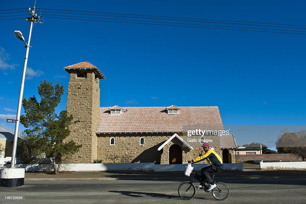 A man rides his bike past a building in Carnarvon on July 20, 2012 in the Northern Cape, South Africa. The town, which has a population of 6000, is the home of the KAT-7 telescope and will host the Square Kilometre Array radio telescope. Due to these developments the town's economy is growing.