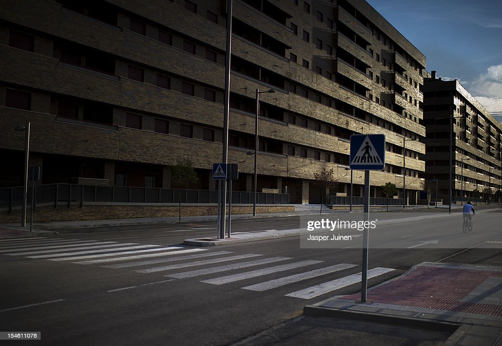 A man rides his bike past some of the many empty newly built apartment buildings with their exterior window shutters closed on October 22, 2012 in Sesena, Spain. With a housing backlog of more than 1.2 million unsold newly build homes, banks in Spain have recenlty started to sell their real estate assets with discounts, some upto 80 percent, slashing prices to a level not seen for over 20 years. With morgages of 100 percent, some experts worry that mistakes from the past are repeated again.