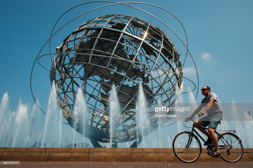 A man rides his bike past the fountains at the Unisphere steel structure at Flushing Meadows-Corona Park, August 22, 2017 in the Queens borough of New York City. With heat index values near 100, the New York City area is under a heat advisory on Tuesday.