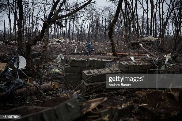 A man rides his bike through a desimated battlefield where the Ukrainian army was defeated by proRussian rebels on March 2 2015 on the outskirts of...