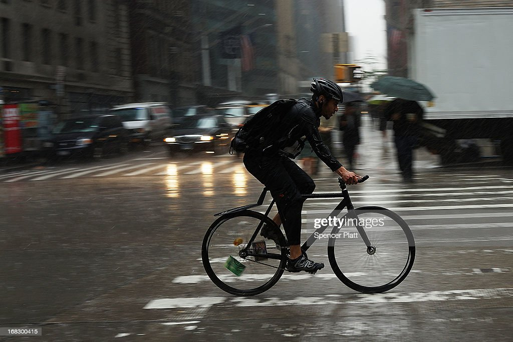 A man rides his bike through the street during a rain storm on May 8, 2013 in New York City. After experiencing an unusually dry spring in recent weeks, New York was hit with heavy rain Wednesday that resulted in numerous flash floods and heavy downpours.