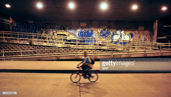 A man rides his bike under a bridge painted with graffiti on July 26 2009 in Cali department of Valle del Cauca Colombia Hundreds of graffiti can be...