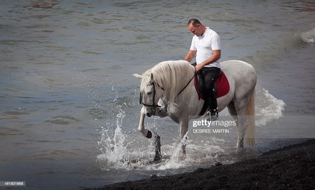 A man rides his horse into the surf at la Enramada beach (La Caleta) along the southern Adeje coastline on the Canary island of Tenerife, on January 20, 2015 during the annual pilgrimage marking the Saint Sebastian, considered the patron protector of animals against pests and disease. The San Sebastian festivities in Adeje began at the end of the 19th century and start with a traditional mass and blessing of the Saint's effigy that is then carried on the shoulders of the parishioners to the sea shore.