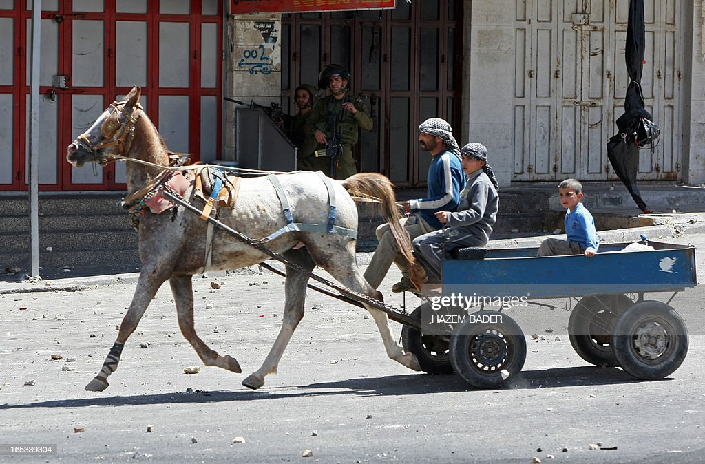 A man rides his horse past Israeli security forces during clashes with Palestinian stone throwers following a demonstration demanding the release of Palestinians detained in Israeli jails in the West Bank town of Hebron on April 3, 2013. Palestinians across the West Bank and Gaza were observing a general strike, with prisoners refusing food to mourn the death of a fellow inmate in an Israeli jail. AFP PHOTO/HAZEM BADER