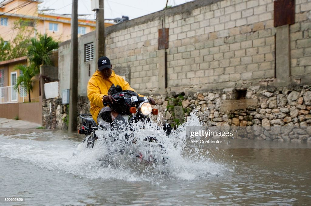 A man rides his motorbike through a flooded street in Punta Cana, in the eastermost tip of the Dominican Republic as Hurricane Maria passes just north of the La Espanola island the country shares with Haiti, on September 21, 2017. After cutting a devastating path across Puerto Rico, the now Category Three storm, packing 115 mile (185 kilometre) per hour winds, is passing north of the Dominican Republic as it moves toward the Turks and Caicos Islands, according to the US National Hurricane Centre. / AFP PHOTO / Erika SANTELICES