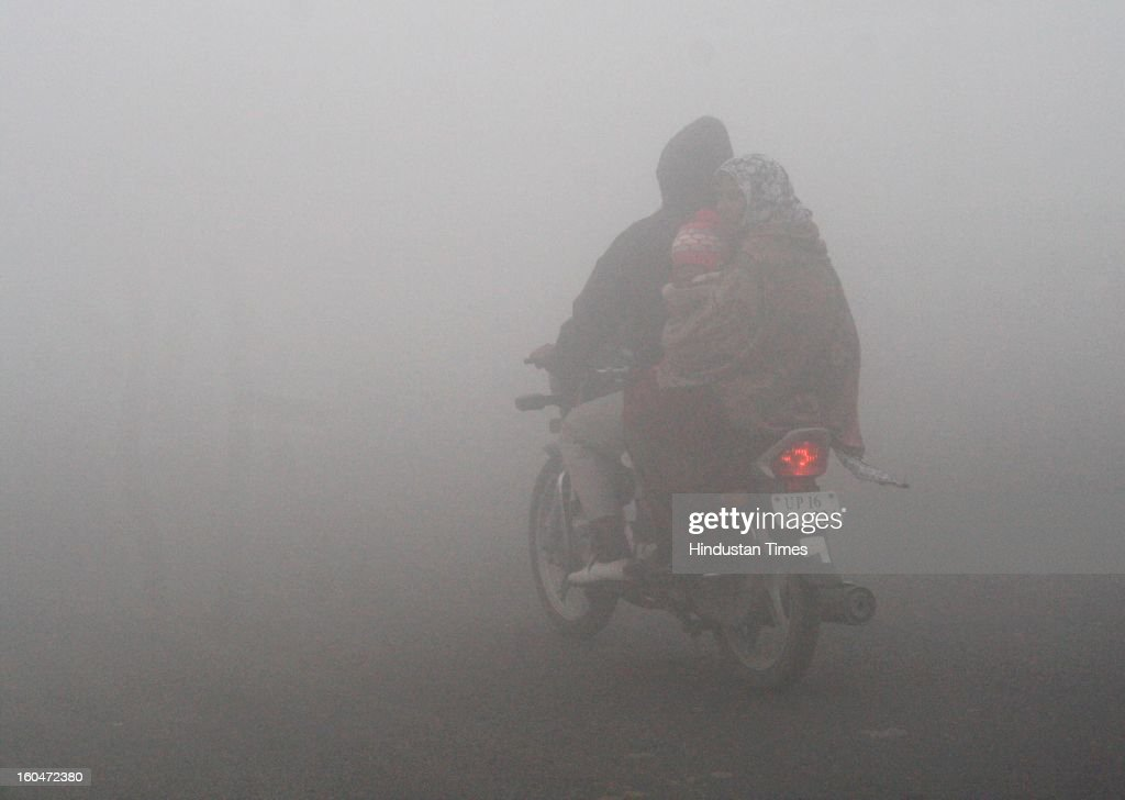A man rides his motorcycle amid thick fog on February 1, 2013 in Noida, India. Dense fog in Delhi NCR badly affected the daily life of people as visibility, dropped to less than 50 m. This led to the cancellation of 10 trains and delaying over 130 flights, diversions and cancellations of 19 each.
