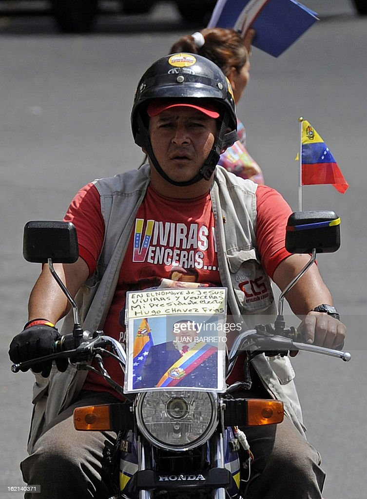 A man rides his motrobike in the surroundingas of the military hospital in Caracas, where Venezuelan President Hugo Chavez was hospitalized following his return from Cuba on the eve, on February 19, 2013. Chavez returned to Venezuela early on Monday after spending more than two months in Cuba for cancer surgery and treatment, announcing his surprise homecoming via Twitter. 'We have arrived again to the Venezuelan motherland,' Chavez wrote. AFP PHOTO/Juan Barreto