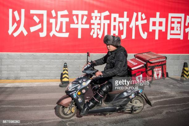 A man rides his scooter past a board that reads 'For a new era in China with Xi Jinping' in Beijing on December 7 2017 / AFP PHOTO / Fred DUFOUR