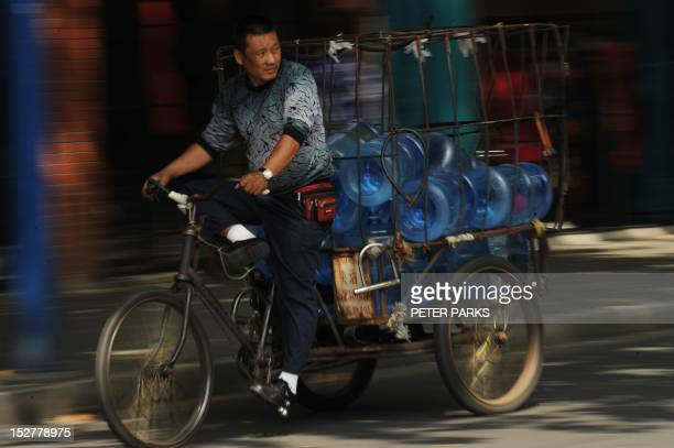 A man rides his tricycle carrying bottled water on a street in Shanghai on September 26 2012 Japanese Prime Minister Yoshihiko Noda warned China in...