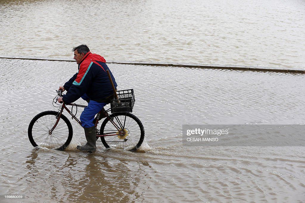 A man rides on a flooded road following the rise of the River Ebro, due to heavy rainfall, in Novillas, near Zaragoza, on January 22, 2013. AFP PHOTO / CESAR MANSO